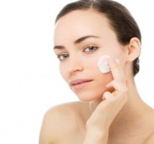 A girl rubbing cream on her face to get rid of pimples